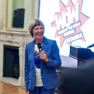 Jude Kelly, sarı saçları ense hizasına uzanan, beyaz tenli, 60'larında bir kadın. Mavi ceket ve pantolon giymiş, Woman of the World festivalinde elinde mikrofonla sunum yapıyor. Gülümsüyor ve dişleri görünüyor.