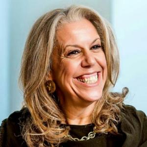 Stevie Spring, omuz hizasında kumral saçları olan, esmer tenli, siyah gözlü 60'larında bir kadın. Gülümsüyor ve dişleri görünüyor. Koyu yeşil hırka giymiş, boynunda birbirine geçmiş yuvarlaklardan oluşan zincir şeklinde bir kolye var.