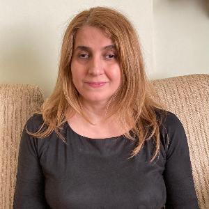 Arzu Şenyurt, omuz hizasında sarı saçları olan, buğday tenli, 40'larında bir kadın. Uzun kollu siyah bluz giymiş, kahverengi bir kanepede oturuyor.