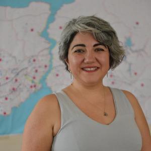 Zelal Yalçın, üst kulak hizasında sarı-siyah saçlarıyla, kahverengi gözlü, buğday tenli 30'larında bir kadın. Gülümsüyor ve dişleri görünüyor. Gri bir askılı giymiş, İstanbul haritasının seçilebildiği bulanık arka planda ayakta duruyor.