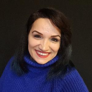 Gamze Elibol, omuzlarına uzanan kahverengi-kızıl saçlı, ela gözlü, beyaz tenli, 40'larında bir kadın.Mavi boğazlı kazak giymiş, gülümsüyor ve dişleri görünüyor.