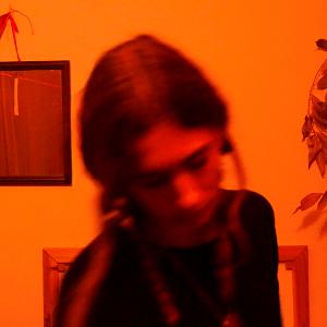 Heka, arkasında toplanmış saçlarıyla, 30'larında bir kadın. Fotoğraf bulanık olduğu için Heka kolaylıkla seçilemiyor. Arkasındaki turuncu duvar üstünde kare şeklinde ayna ve yapraklı bir dal görünüyor.