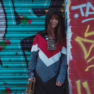 Yazz Ahmed, omuzlarına kadar uzanan kahverengi saçlarıyla, buğday tenli, 30'larında bir kadın. Başını bir kapişonla kapatmış. Boynunda dağınık şekillerden oluşan kolyeler görünüyor, elinde bir trompet tutuyor. Üst tarafı birbirini takip eden kırmızı, beyaz ve gri oklardan oluşan, etek kısmı düz siyah renk bir elbise giymiş, sprey boya ile boyanmış kırmızı duvara dayanarak gülümsüyor.