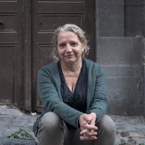 Hacer Foggo, sarı saçları arkada toplanmış, beyaz tenli, 50'lerinde bir kadın. Ahşap eski bir kapı önünde kaldırıma oturmuş, ellerini dizleri önünde birleştirmiş, gülümsüyor.