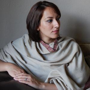 Saima Mir, omuzarına uzanan kızıl-kahverengi saçlı, beyaz tenli, 40'larında bir kadın. Ellerini oturduğu kanepenin kolçağında birleştirmiş sola bakıyor.