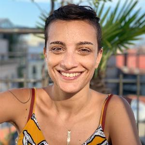Nora Tataryan, esmer tenli, ela gözlü, kısa saçları başının üstünde toplanmış, 30'larında bir kadın. Askılı sarı elbise giymiş, gülümsüyor ve dişleri görünüyor.