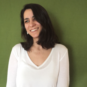 Melis Cankara, omuzlarına uzanan düz siyah saçlı, beyaz tenli, siyah gözlü, 40'larında bir kadın. Yeşil duvar önünde uzun kollu beyaz bluz giymiş, gülümsüyor.