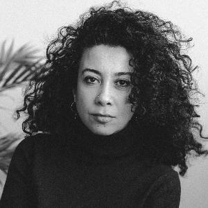 Hazal Halavut, omuzlarına uzanan siyah kıvırcık saçlı, siyah gözlü 30'larında bir kadın. Siyah bir kazak giymiş, bir eliyle diğer kolunu tutuyor. Fotoğraf siyah beyaz.