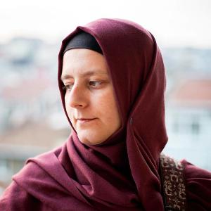 Rümeysa Çamdereli, kırmızı başörtülü, beyaz tenli, yeşil gözlü, 40'larında bir kadın. Başını sağa çevirmiş, omzunda çantasının bordo askısı görünüyor.