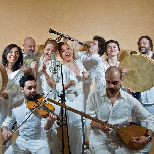 Kardeş Türküler, herkesin beyaz giydiği ve gülümsediği 4 kadın ve 5 erkekten oluşan müzik grubu. Fotoğrafın önünde keman ve bağlama çalan iki erkek oturuyor. Arkalarında soldan sağa elinde bendir tutan bir kadın, cümbüş çalan saçsız bir erkek, mikrofon önünde şarkı söyleyen iki kadın, klarneti havaya kaldırarak çalan bir erkek, bendir çalan bir başka kadın ve gitar çalan bir erkek görünüyor.