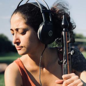 Melisa Yıldırım, omuzlarına kadar uzanan siyah dalgalı saçlarıyla, buğday tenli, siyah gözlü 30'larında bir kadın. Yeşil bir kazak giymiş, yalnızca akort burguları gözüken bir enstrumanı tutarak gülümsüyor.