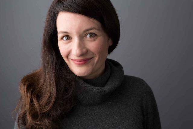 Pelin Turgut, omuzlarına uzanan kahverengi saçlarıyla, beyaz tenli, ela gözlü, 40'larında bir kadın. Siyah boğazlı kazak giymiş, gri duvarın önünde gülümsüyor.